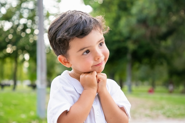 Doce menino alegre de pé e posando no parque de verão, apoiando o queixo nas mãos, sorrindo e olhando para longe. tiro do close up. conceito de infância