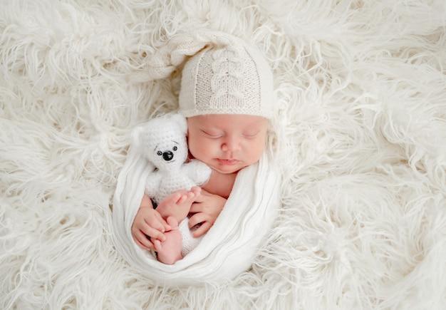 Doce menino recém-nascido com chapéu de malha dormindo com ursinho de pelúcia em pelo branco e segurando as pernas com as mãos