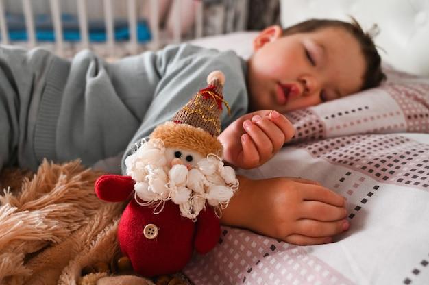 Doce menino toodler caucasiano dormindo em sua cama ao lado de um gnomo de brinquedo