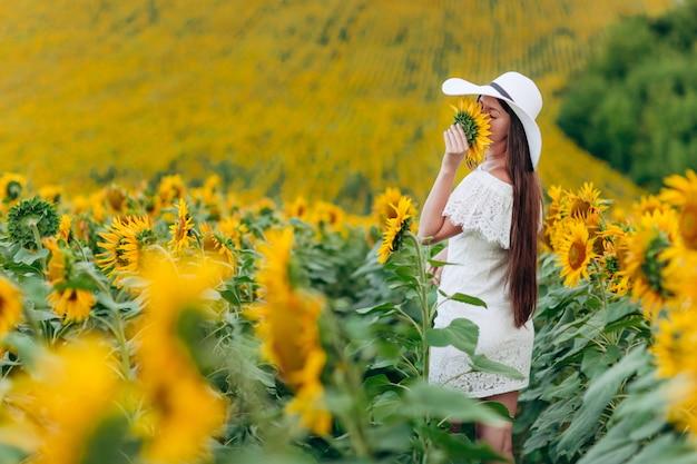 Doce mulher jovem e bonita em um vestido branco e chapéu em um campo de girassóis. garota está segurando o girassol na mão. férias de verâo