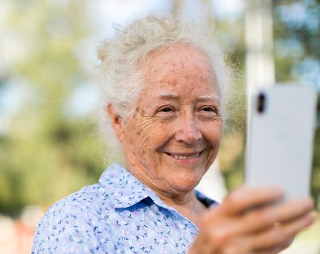 Doce mulher sênior tomando uma selfie