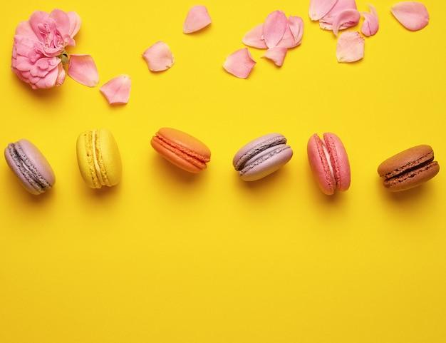 Doce multi colorido macarons com creme e um botão de rosa com pétalas espalhadas
