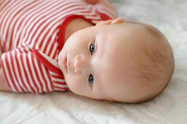Doce pequeno bebê recém-nascido deitado em uma cama