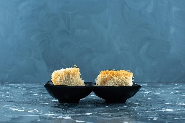 Doce sobremesa turca kadayif em um recipiente, na mesa azul.