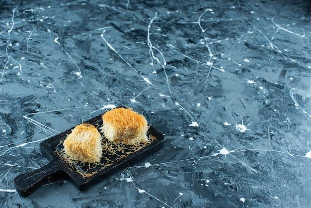 Doce sobremesa turca kadayif em uma placa, na mesa azul.