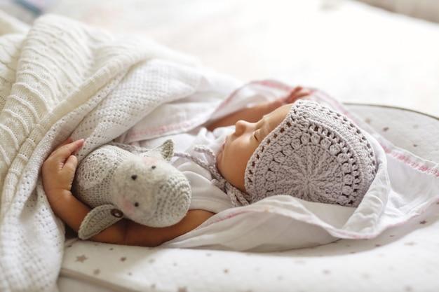 Doce sono recém-nascido no boné retrô com brinquedo artesanal