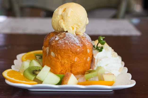 Doce sorvete com frutas fatiadas na mesa de madeira, closeup mix de frutas e sorvete