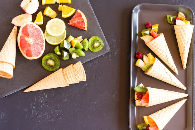 Doce tratamento para o feriado. cones de waffle com fruta madura. vista do topo.