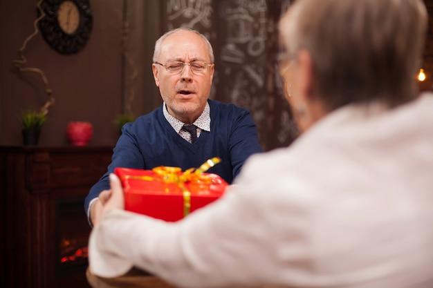 Doce velhinha dando um presente ao marido enquanto estão jantando fora. jantar romântico. casal de idosos.