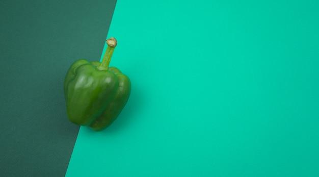 Doce verde fresco ou pimentão plano deitado sobre fundo de textura verde turquesa