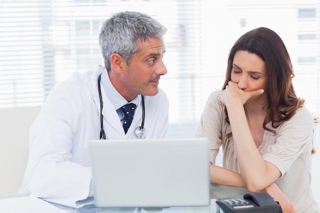 Docer grave mostrando algo no laptop para o paciente
