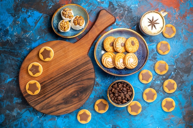 Doces à distância, vista de cima, biscoitos de delícia turca no tabuleiro grãos de café uma xícara de café