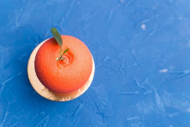 Doces, bolo e delicioso conceito - mousse de sobremesa no formato de uma fruta laranja. superfície azul Foto Premium