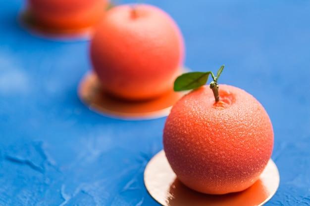 Doces, bolo e delicioso conceito - mousse de sobremesa no formato de uma fruta laranja. Foto Premium