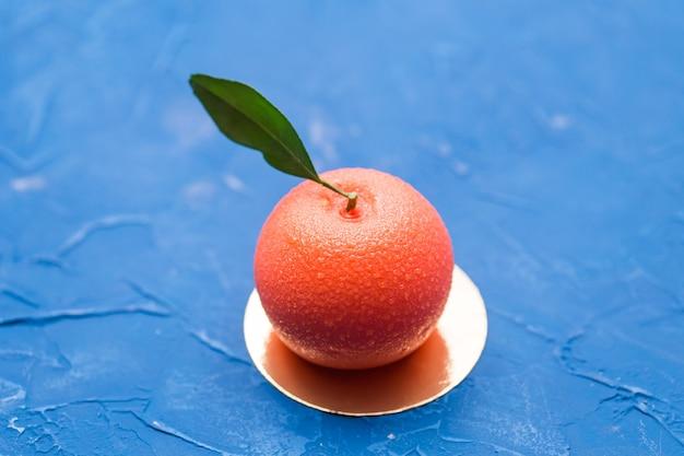 Doces, bolo e delicioso conceito - mousse de sobremesa no formato de uma fruta laranja.