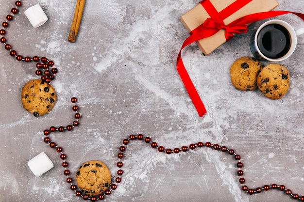 Doces brancos vermelhos, biscoitos, marshmallow, xícara de café e caixa de presente estão no chão cinzento