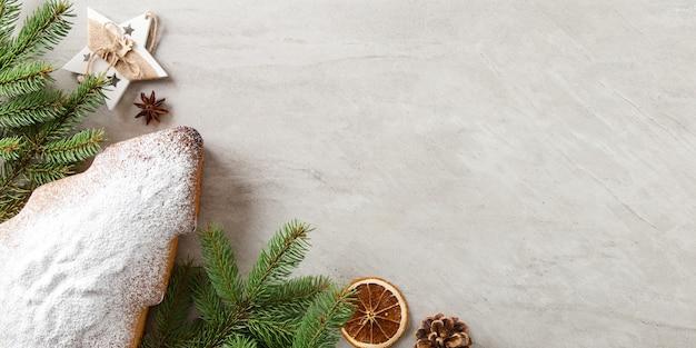Doces caseiros, biscoitos em forma de árvore de natal, ramos de abeto e enfeites em uma mesa de pedra. vista do topo.