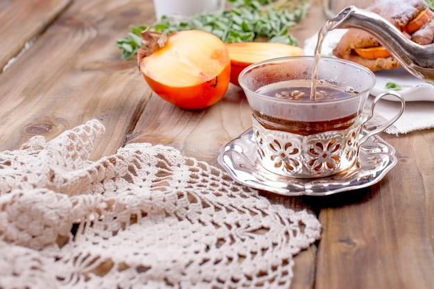 Doces caseiros com caquis, no café da manhã. lindo copo com chá. chaleira. mesa de madeira, toalha de mesa com renda. espaço livre para texto ou publicidade.