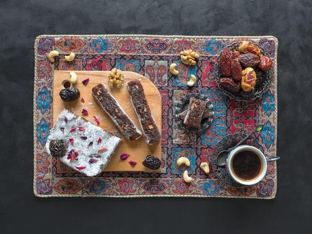 Doces caseiros de marmelada oriental com frutas de data, doces orientais em uma superfície preta