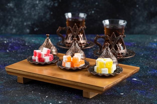 Doces coloridos com chá perfumado na superfície azul