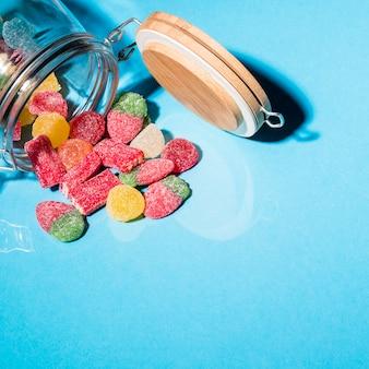 Doces coloridos da geléia de açúcar que derramam o frasco no fundo azul