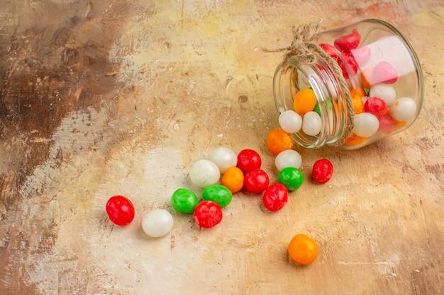 Doces coloridos de frente para dentro da lata de vidro com fundo claro Foto gratuita
