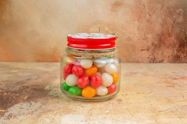 Doces coloridos de frente para dentro da lata de vidro com fundo claro