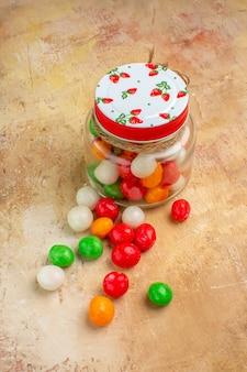 Doces coloridos de frente para dentro de lata de vidro em piso claro
