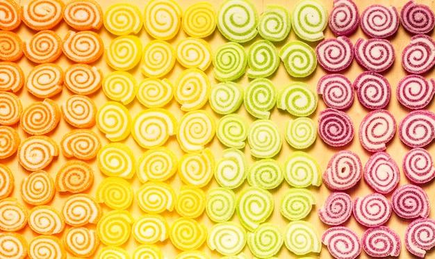 Doces coloridos de geleias e doces em fundo madeira
