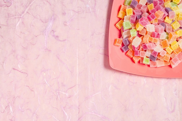 Doces coloridos e geléia no prato de cor em fundo rosa