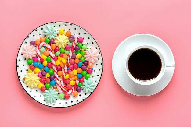 Doces coloridos em um prato e xícara de café