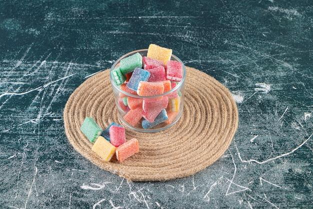 Doces coloridos em uma tigela de vidro em um tripé, sobre a mesa mista.