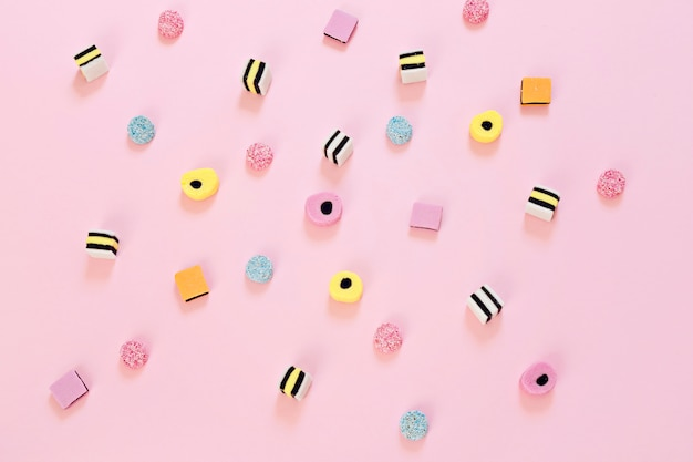 Doces coloridos espalhados no fundo rosa