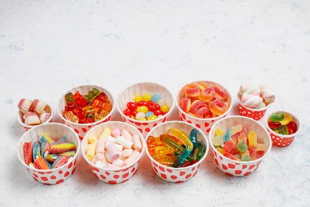 Doces coloridos, geléia, marshmallow na superfície da luz. vista superior com espaço de cópia