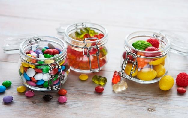 Doces coloridos, geleias e marmeladas em potes sobre a mesa
