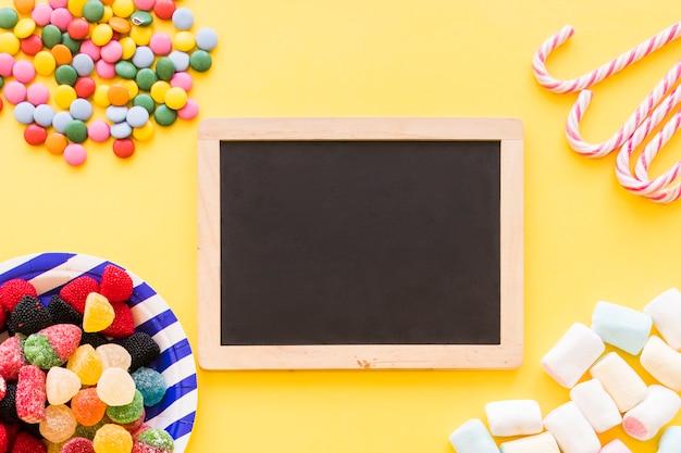 Doces coloridos, hortelã e marshmallow no pano de fundo amarelo