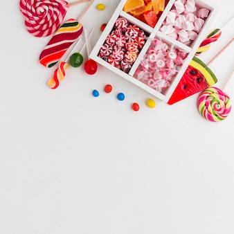 Doces coloridos na mesa branca com espaço de cópia