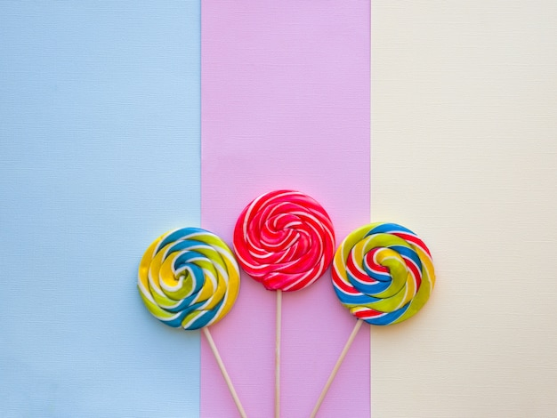 Doces coloridos saborosos diferentes no fundo da cor pastel.