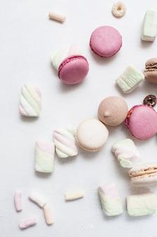 Doces coloridos sobre fundo branco. macaroons, zéfiros e cereais matinais