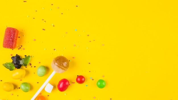 Doces coloridos vívidos no fundo amarelo