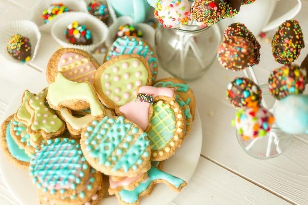 Doces coloridos, xícara e biscoitos na mesa do café