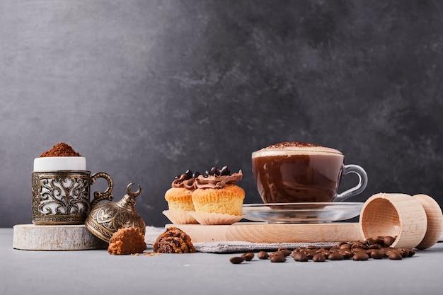 Doces com uma xícara de chocolate quente.