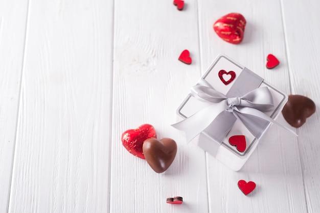 Doces corações e caixa de presente na placa de madeira