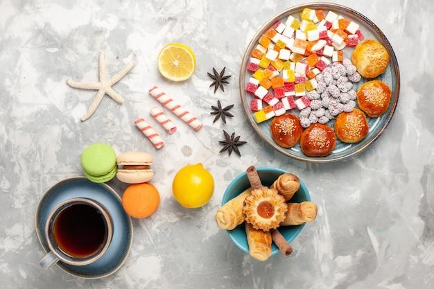 Doces de açúcar de vista de cima com pequenos pãezinhos doces e bagels na superfície branca