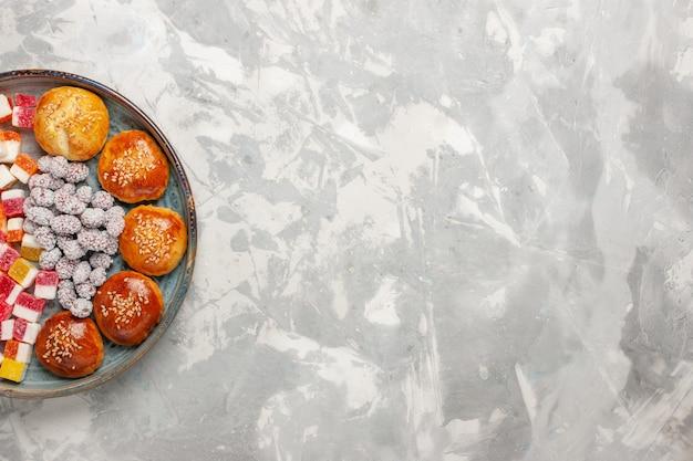 Doces de açúcar de vista superior com pequenos pãezinhos na superfície branca