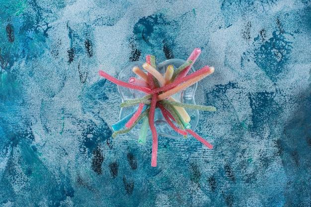 Doces de alcaçuz coloridos em um copo, na mesa de mármore.