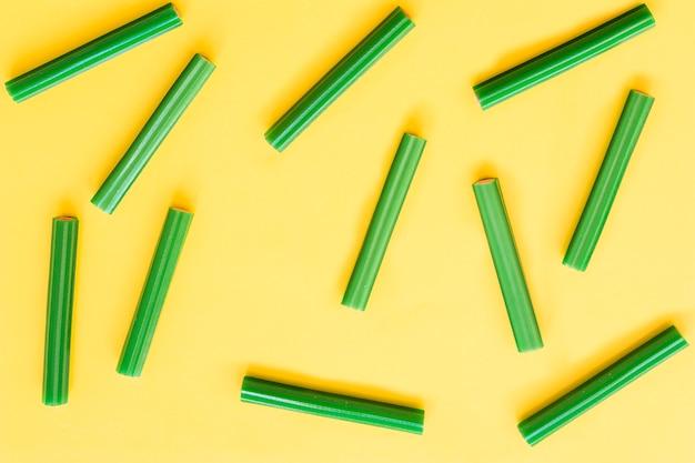 Doces de alcaçuz verde sobre fundo amarelo