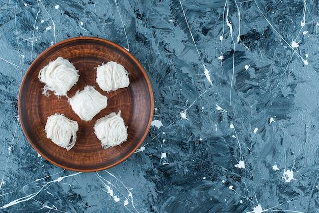 Doces de algodão turco tradicionais em uma placa de madeira, na mesa azul.