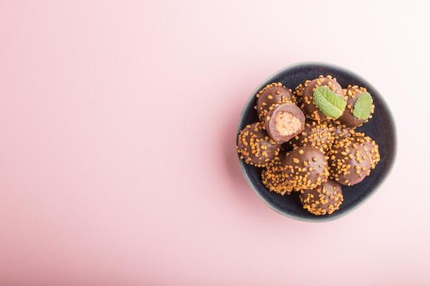 Doces de bola de caramelo de chocolate com amêndoas em um fundo rosa pastel. vista superior, copie o espaço.