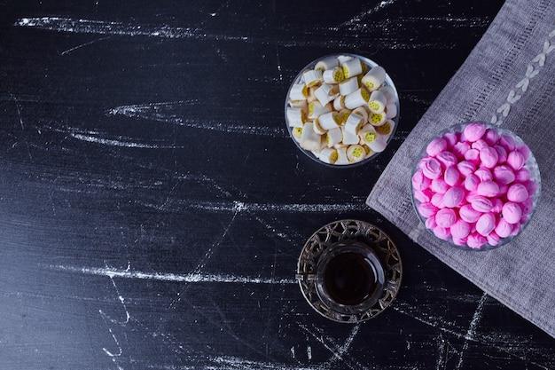 Doces de caramelo com um copo de chá, vista de cima.